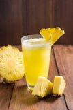 Ananasowy sok i ananasowy plasterek umieszczający na drewnianym tle Obrazy Royalty Free