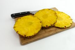 Ananasplakken en mes op hakbord stock afbeeldingen