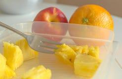 Ananasscheiben in einem Plastik können, eine Metallgabel, eine Orange und eine Nektarine Stockbilder