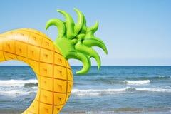 Ananasschwimmenring auf dem Strand Stockfoto