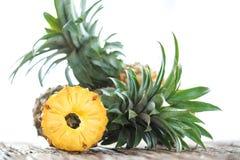 Ananasskiva med kopieringsutrymme på den wood texturbakgrunden Arkivfoton