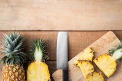 Ananasskiva på träsnittbräde med kniven Arkivbild
