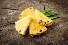 Ananasskivor på wood bakgrund royaltyfri bild