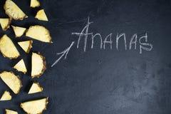 Ananasskivor p? svart bakgrund med utrymme f?r text- och kritainskrift arkivfoton