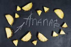 Ananasskivor p? svart bakgrund med utrymme f?r text- och kritainskrift royaltyfri bild