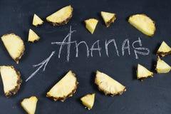 Ananasskivor p? svart bakgrund med utrymme f?r text- och kritainskrift fotografering för bildbyråer