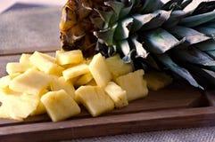 Ananasstukken en Bovenkant op Scherpe Raad Royalty-vrije Stock Afbeelding