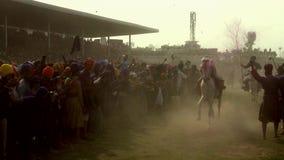Anandpur Sahib, India - 20180302 - Hola Mohalla - Sikh Festival - Mensentribunes op Rug van Twee Paarden stock footage