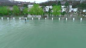ANAPA ΡΩΣΊΑ - 19 01 2019: Δύο αναβάτες επιπλέουν στις ιστιοσανίδες γουλιάς Κολυμπήστε μεταξύ των δέντρων στο παλαιό πλημμυρισμένο απόθεμα βίντεο