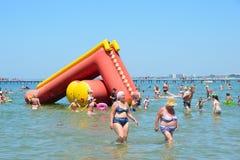 Anapa, Россия, 13-ое июля 2017 2 женщины приходят из воды к гостинице Anapa пляжа города Стоковые Фотографии RF