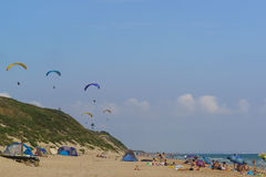 Anapa område Krasnodar Krai Ryssland - Augusti 15 2015: Paragliders som skjuta i höjden över den lösa sandiga stranden med tält o Royaltyfri Bild