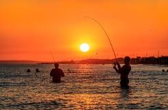Anapa, Rússia - 9 de agosto de 2015: Pescadores que pescam com as varas de pesca que estão meias na água do mar no por do sol do  Foto de Stock