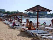 ANAPA, RUSLAND - JUNI 2011: De vakantiegangers bij strand nemen het verbergen van stadsanapa in schaduw onder eaves zijn toevluch Royalty-vrije Stock Foto's
