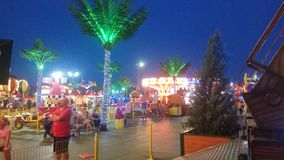 People rest in amusement park at early evening time