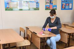 Anapa, Russia - March 27, 2020: The girl pours cleaning and disinfectant on the desk at the school during the quarantine period