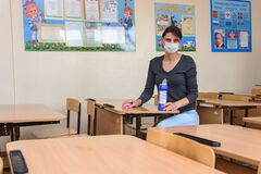Anapa, Russia - March 27, 2020: Girl washes a school desk with a cleaner