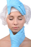 Anaplasty. Examining face before surgery. Portrait of beautiful young woman in medical headwear looking at camera while hands in gloves examining her face royalty free stock photos