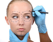 Anaplasty. Making marks on face. Portrait of beautiful young woman looking away while doctors hands in gloves making marks on her face isolated on white stock photography