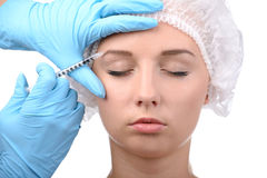 Anaplasty. Medical injection. Portrait of beautiful young woman in medical headwear looking away while hand in glove making an injection in her face isolated on royalty free stock photo