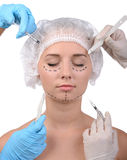 Anaplasty. Plastic surgery. Terrified young woman looking away while many hands holding syringes and scalpels near her face royalty free stock photo