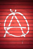 Anarchy sign. Painted on red wall in white color Royalty Free Stock Image