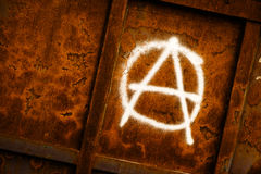 Anarchy symbol graffiti. Spray painted on grunge corroded metal wall Stock Image