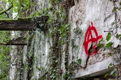 The `Anarchy` symbol graffitied in a ruined stock image