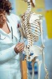 Anatomía de enseñanza de la mujer del médico usando el esqueleto humano Imagen de archivo libre de regalías