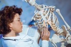 Anatomía de enseñanza de la mujer del médico usando el esqueleto humano Foto de archivo libre de regalías
