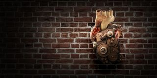 Anatomic heart made with gears and mechanic parts. Anatomic heart model made with gears and mechanic parts, brickwall background stock images