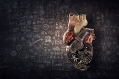 Anatomic heart made with gears and mechanic parts. Anatomic heart model made with gears and mechanic parts, chakboard sketch background royalty free stock photo