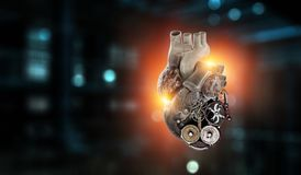 Anatomic heart made with gears and mechanic parts. Anatomic heart model made with gears and mechanic parts, digital board background royalty free stock photo
