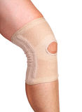 Anatomic knee joint orthosis on leg. Elastic compression bandage. Isolated on white background stock images