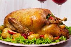 Anatra di arrosto con la patata, le mele, l'insalata, il timo ed i rosmarini Due vetri di vino rosso Fotografie Stock Libere da Diritti