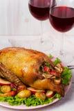 Anatra di arrosto con la patata, le mele, l'insalata, il timo ed i rosmarini Due vetri di vino rosso Immagini Stock