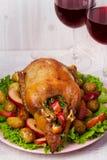 Anatra di arrosto con la patata, le mele, l'insalata, il timo ed i rosmarini Due vetri di vino rosso Fotografia Stock Libera da Diritti