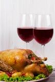 Anatra di arrosto con la patata, le mele, l'insalata, il timo ed i rosmarini Due vetri di vino rosso Fotografia Stock