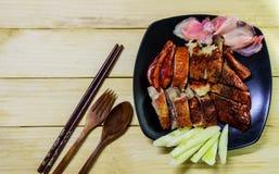 Anatra e verdure di arrosto in banda nera ed in forcella di legno, cucchiaio con salsa su fondo di legno Immagine Stock