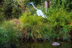 Anatra sullo stagno circondato da alta erba con la statua dell'uccello fotografia stock