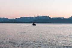 Anatre e piccola barca su un lago blu Immagine Stock Libera da Diritti