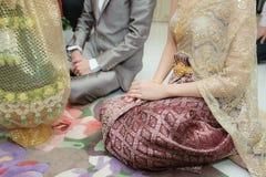 Anbetung übergibt den Ring, der die siamesische geheiratete Kleidung wedding ist Lizenzfreies Stockfoto