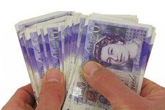 Anbieten einer Handvoll Geldes lizenzfreie stockbilder