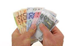 Anbieten einer Handvoll Geldes Lizenzfreie Stockfotos