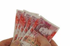 Anbieten einer Handvoll Geldes stockfotografie