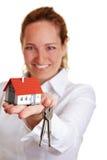 Anbietenhaustasten der Grundstücksmaklerfrau Stockfotografie