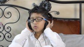 Anblickar för exponeringsglas för liten indisk asiatisk caucasianpojke som bärande lyssnar tycka om musik på stängande ögon och h