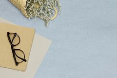 Anblickar på den gula anmärkningsboken, rosa legitimationshandlingar, korg med blommor royaltyfria foton