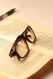 Anblickar skriver och en öppen bok arkivfoto