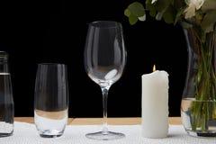 Anbud blommar i vas med vattenflaskan och tomma exponeringsglas på tabellen bredvid stearinljuset Arkivbild
