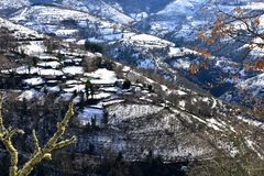Small mountain village on a snowy slope with trees. Ancares Region, Lugo Province, Galicia, Spain. royalty free stock photos